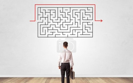 Photo for Businessman in doubt looking to a maze and searching the way out - Royalty Free Image