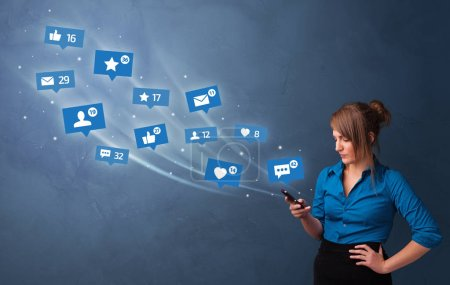 Photo for Young person using phone with flying social media icons around - Royalty Free Image