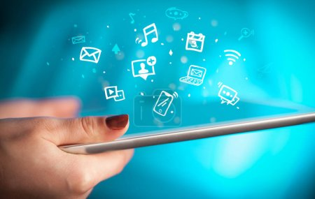 Photo pour Main tenant la tablette avec le multimédia dessiné et les icônes d'application - image libre de droit