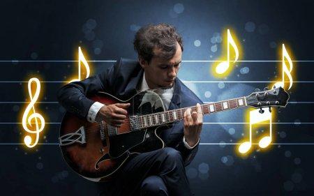 Photo pour Jeune beau guitariste jouant avec fond de feuille de musique - image libre de droit