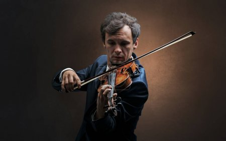 Photo for Lonely violinist composing on cello with nothing around - Royalty Free Image