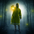 Man in raincoat coming from dark forest with glowi...