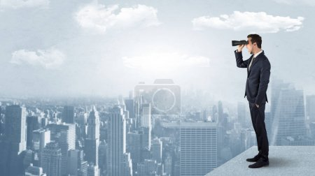 Photo for Businessman looking forward to a city  with binoculars from skyscraper concept - Royalty Free Image