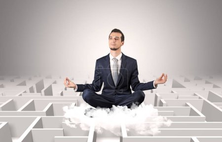 Photo for Young businessman meditate in yoga position on a cloud with infinity maze concept - Royalty Free Image