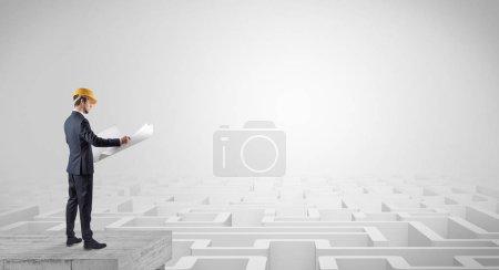 Photo pour Architecte debout sur labyrinthe et regardant un plan futur - image libre de droit