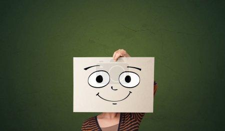 Foto de Joven estudiante sosteniendo un papel con emoticono riéndose delante de su cara - Imagen libre de derechos