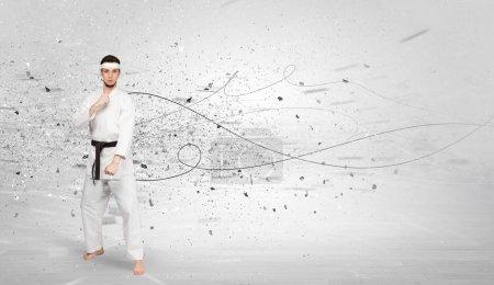 Photo pour Jeune entraîneur de karaté faisant des tours de karaté avec un concept chaotique - image libre de droit