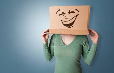 Photo for Young girl standing and gesturing with a cardboard box on her head - Royalty Free Image
