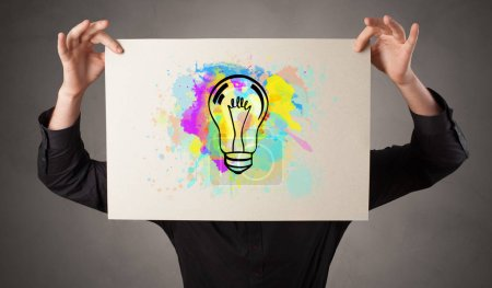 Person holding a paper with colorful bulb concept