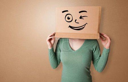 Photo pour Jolie femme debout et gesticulant avec une boîte en carton sur la tête - image libre de droit