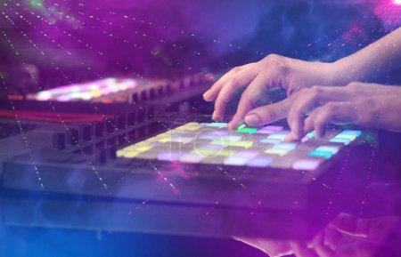 Photo pour Mélange de musique sur contrôleur midi avec les couleurs du club parti autour à la main - image libre de droit