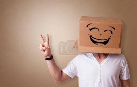 Photo pour Jeune homme au visage heureux illustré boîte en carton sur sa tête - image libre de droit