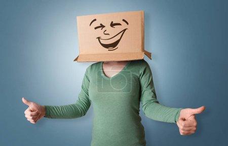 Photo pour Jeune fille debout et gestuelle avec une boîte en carton sur la tête - image libre de droit