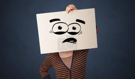 Photo pour Personne occasionnelle tenant un papier avec émoticône drôle devant son visage - image libre de droit