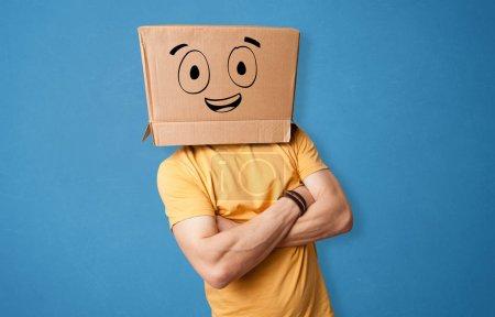 Photo pour Jeune homme debout et gesticulant avec une boîte en carton sur la tête avec un visage souriant dessiné - image libre de droit