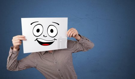 Photo for Young student holding a paper with laughing emoticon in front of his face - Royalty Free Image