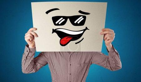 Foto de Persona casual sosteniendo un papel con emoticono fresco delante de su cara - Imagen libre de derechos
