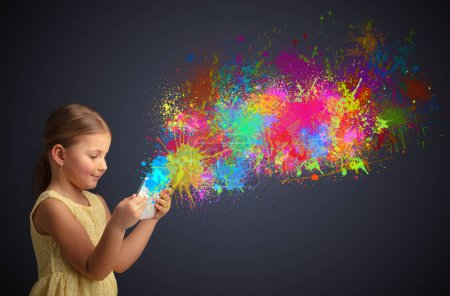 Photo for Cute little girl using tablet with colourful splash concept - Royalty Free Image