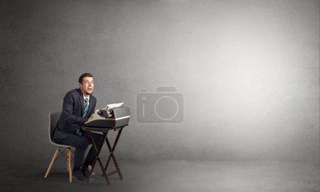 Photo pour Homme travaillant dur sur une machine à écrire dans un espace vide - image libre de droit