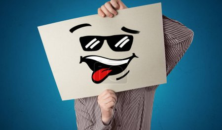 Photo pour Personne occasionnelle tenant un papier avec émoticône cool devant son visage - image libre de droit