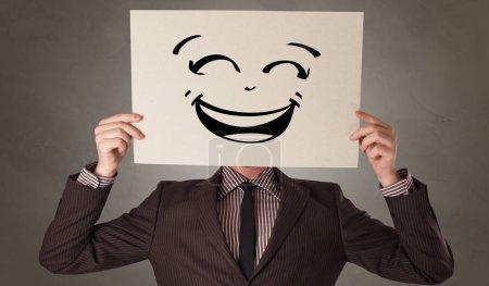 Foto de Persona casual sosteniendo un papel delante de su cara con cara de emoticono dibujado - Imagen libre de derechos