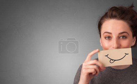 Personne tenant devant sa bouche une carte