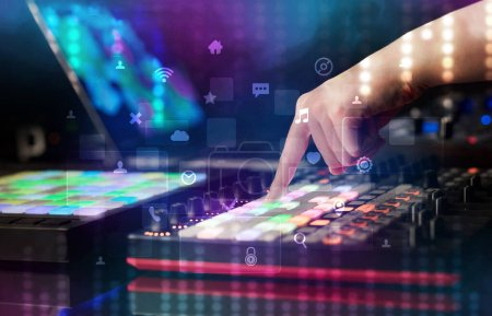 Photo pour Mélange de musique sur contrôleur dj avec les médias sociaux icônes du concept à la main - image libre de droit