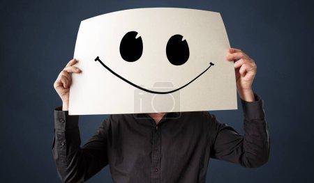 Foto de Persona casual sosteniendo un papel con emoticono divertido delante de su cara - Imagen libre de derechos