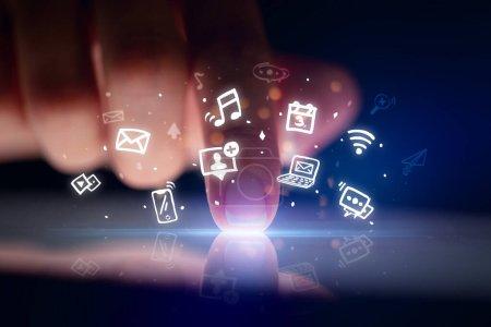 Photo pour Comprimé tactile doigt avec icônes d'application hologramme et fond sombre - image libre de droit