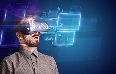 Foto de Hombre de negocios mirando a través de gafas de Realidad Virtual con inscripción ARQUITECTURA DE DATOS, concepto de nueva tecnología - Imagen libre de derechos