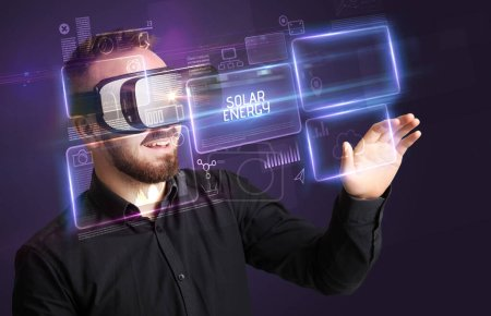 Photo for Businessman looking through Virtual Reality glasses with SOLAR ENERGY inscription, new technology concept - Royalty Free Image