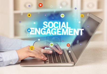 Photo for Freelance woman using laptop with SOCIAL ENGAGEMENT inscription, Social media concept - Royalty Free Image