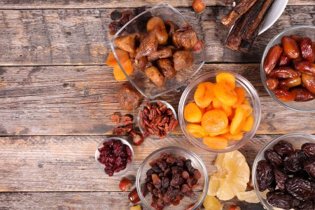 assorted dried fruit served on wooden table