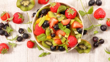 Photo for Mixed fruit salad in bowl on wooden table - Royalty Free Image