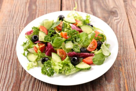 Photo for Vegetable salad mixed on wooden table - Royalty Free Image