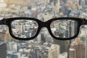 cityscape view focused in glasses lenses, vision concept
