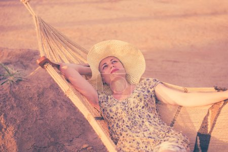 Photo for Pretty woman in hat portrait on hammock at sunset beach - Royalty Free Image
