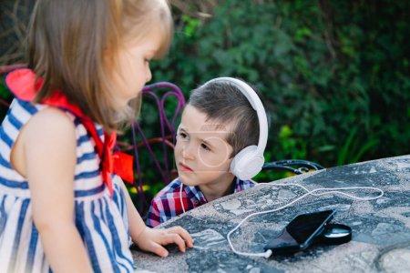 Photo pour Frères écoutant de la musique avec écouteurs à l'extérieur - image libre de droit