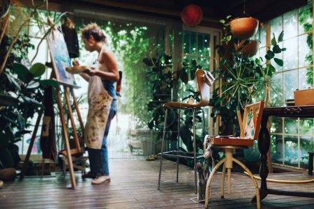 Photo pour Tir intérieur d'artiste féminine professionnelle, peinture sur toile en studio avec des plantes. - image libre de droit