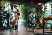 """Постер, картина, фотообои """"Крытый выстрел профессиональной артисткой, живопись на холсте в студии с растениями."""""""