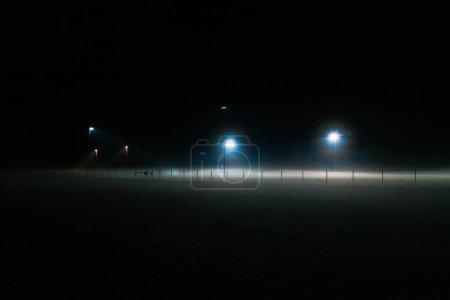 Photo pour Terrain de football solitaire couvert de brouillard la nuit seulement illuminé par des projecteurs - image libre de droit