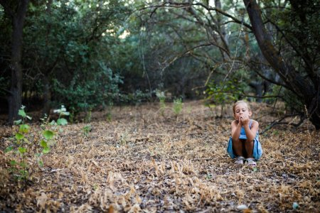 Photo pour Petite fille solitaire et triste accroupie dans la forêt. Concept des sentiments . - image libre de droit