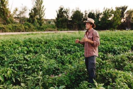 Photo pour Jeune fermier avec chapeau travaillant dans son champ - image libre de droit