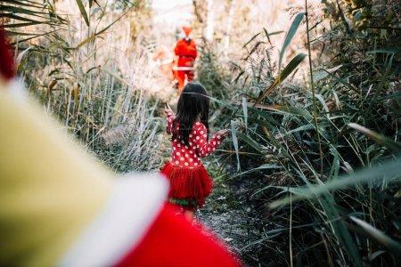 Photo pour Fille déguisée à Noël dans la forêt avec leur famille - image libre de droit
