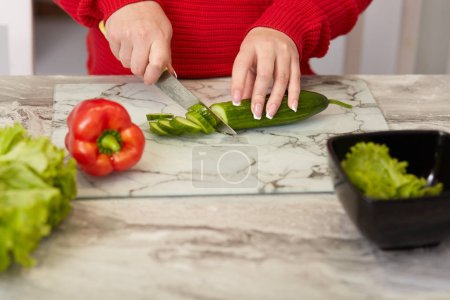 Photo for Cropped image of womans hands cuts vegetables with knife, slices cucumber, pepper and lettuce at kitchen table, prepares vegeterian fresh salad, dressed in red clothes, has manicure. Cooking concept - Royalty Free Image