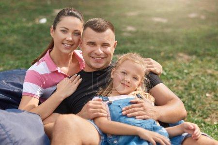 Photo pour Jeune famille avec le doughter adorable ayant l'amusement dans la nature, s'asseyant sur la présidence sans cadre, regardant souriant à l'appareil-photo, utilisant des tenues occasionnelles. Concept de famille, d'enfance, de relation et de hapyyness. - image libre de droit