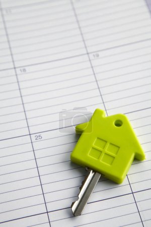 Key and house on calendar background