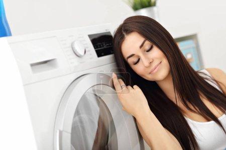Photo pour Photo de jeune femme au foyer avec buanderie à côté de la machine à laver - image libre de droit