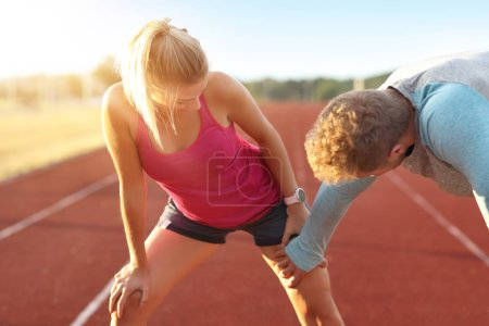 Photo for Picture showing man and woman racing on outdoor track - Royalty Free Image