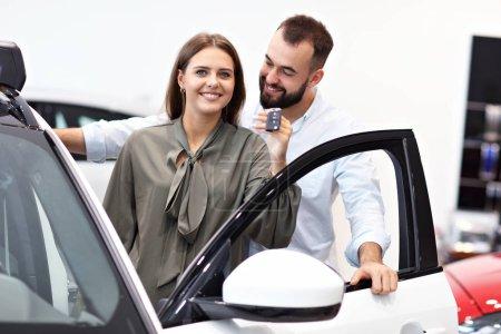Photo pour Image de couple adulte choisissant une nouvelle voiture dans le showroom - image libre de droit